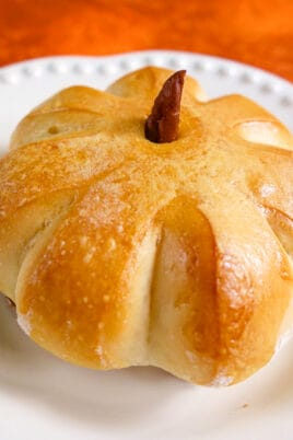 baked rolls that are pumpkin shaped on a plate