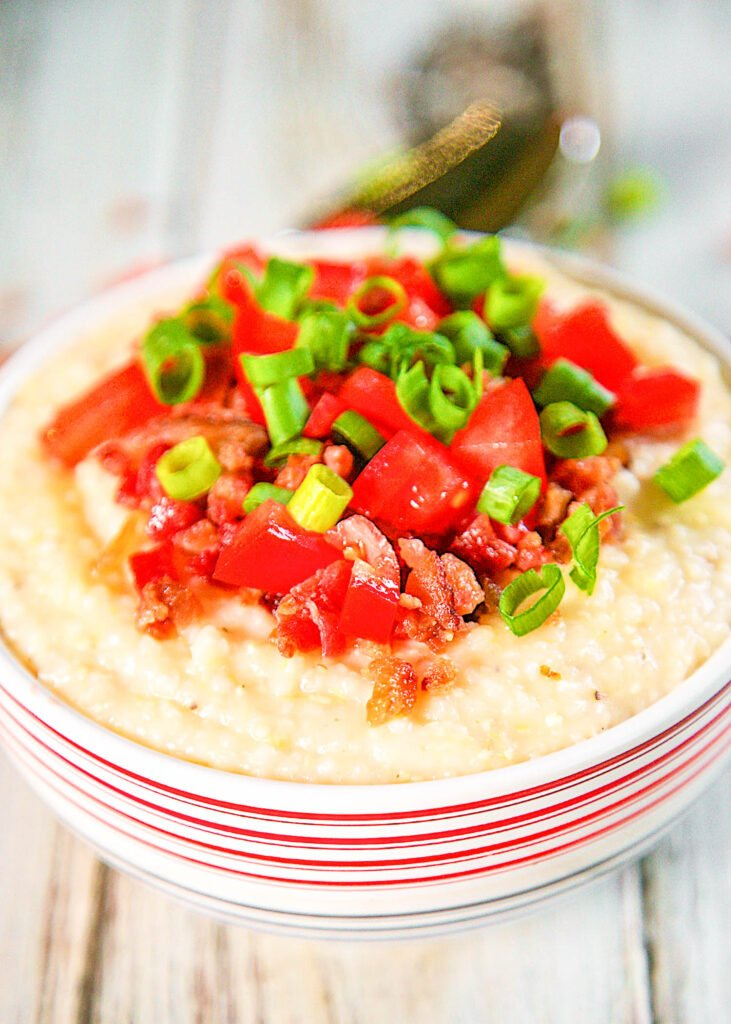 bowl of grits topped with bacon, tomatoes and green onions
