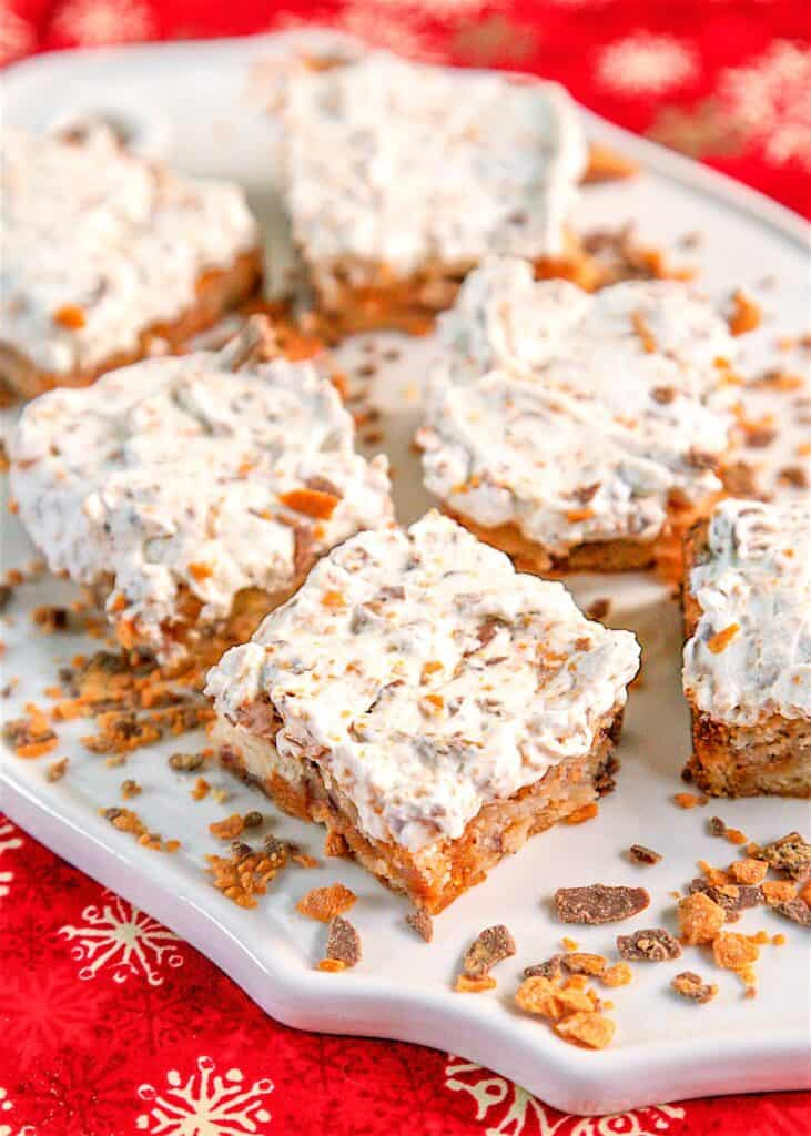 platter of butterfinger shortbread bars with whipped cream topping