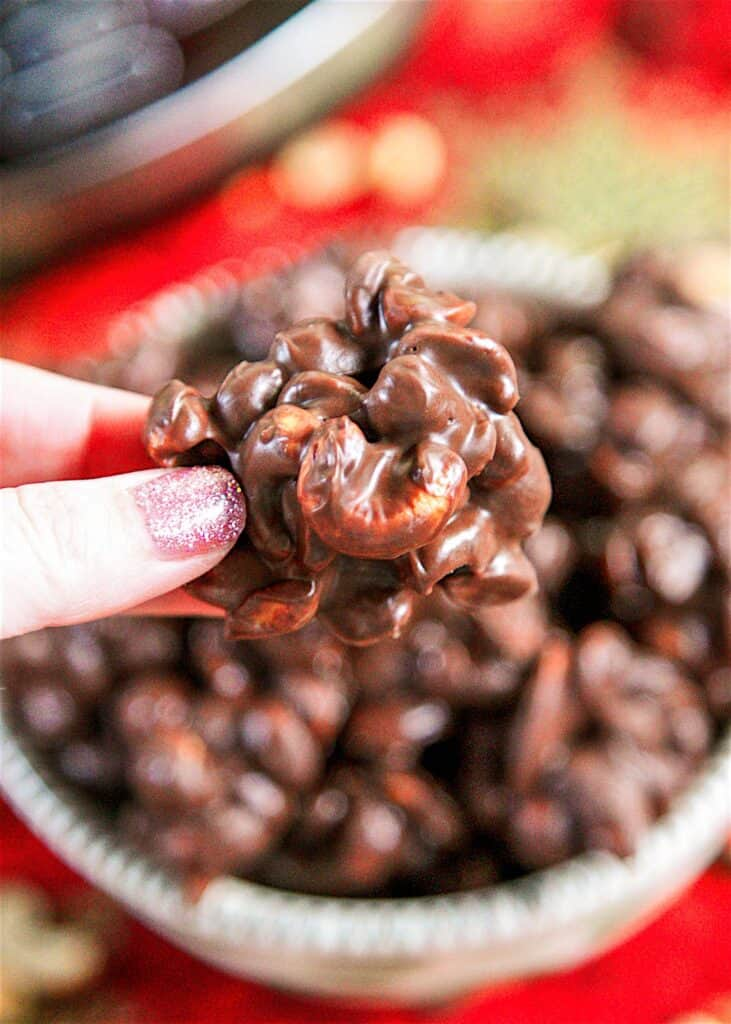 holding a chocolate covered peanut cluster