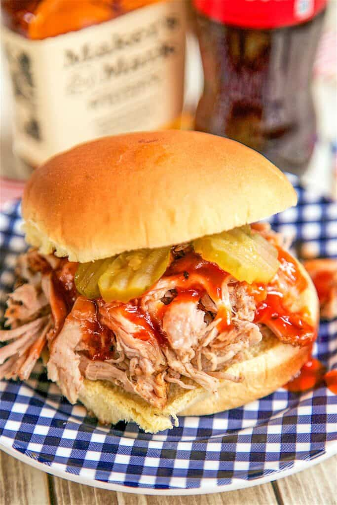 pulled pork sandwich with pickles on a plate