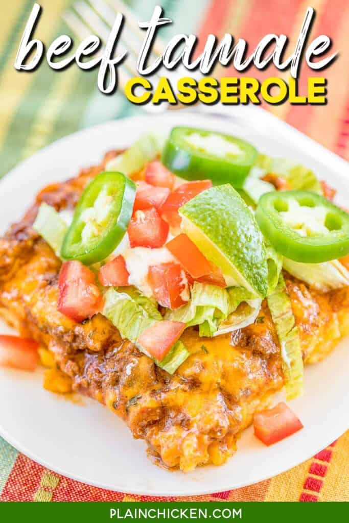 slice of beef tamale casserole on a plate topped with lettuce tomatoes and lime
