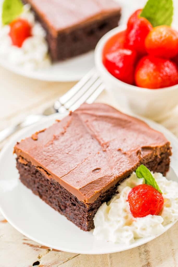 slice of chocolate cake on a plate with whipped cream and strawberries