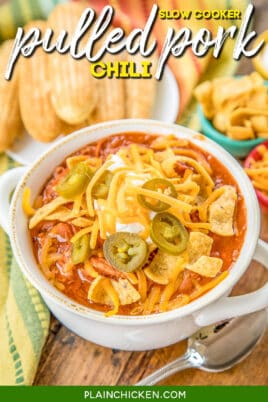 bowl of pulled pork chili topped with sour cream, cheese, and jalapenos