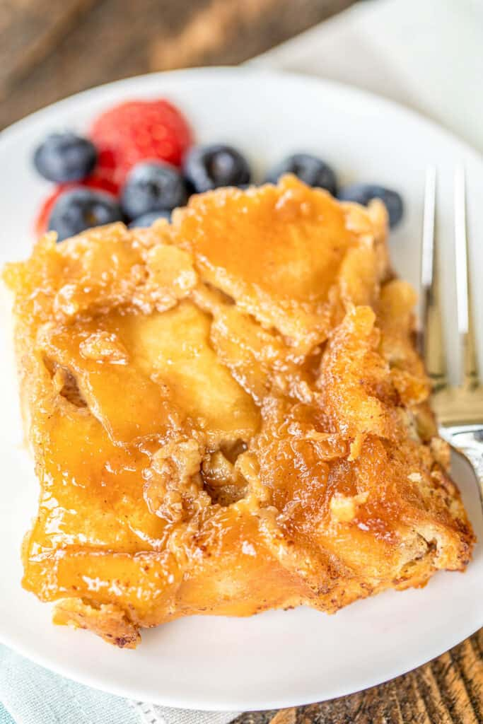 slice of french toast casserole on a plate with fruit