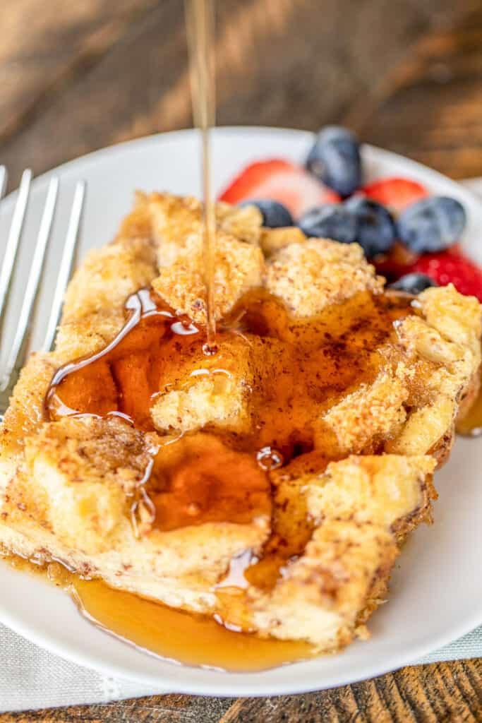 pouring syrup over a slice of french toast casserole on a plate with fruit