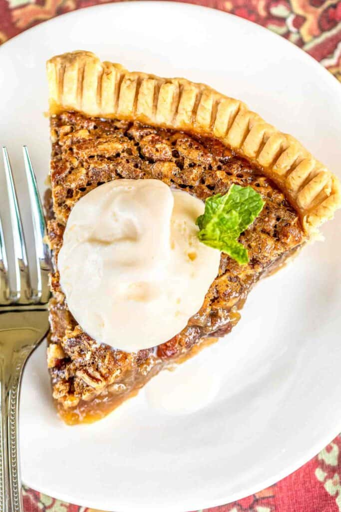 slice of pecan pie topped with ice cream on a plate