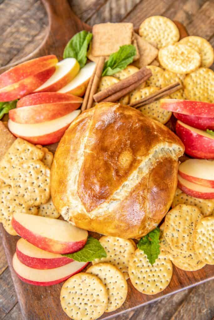 Baked brie on a platter with crackers and apples