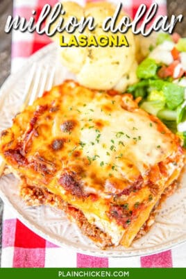 slice of million dollar lasagna on a plate with salad and a roll
