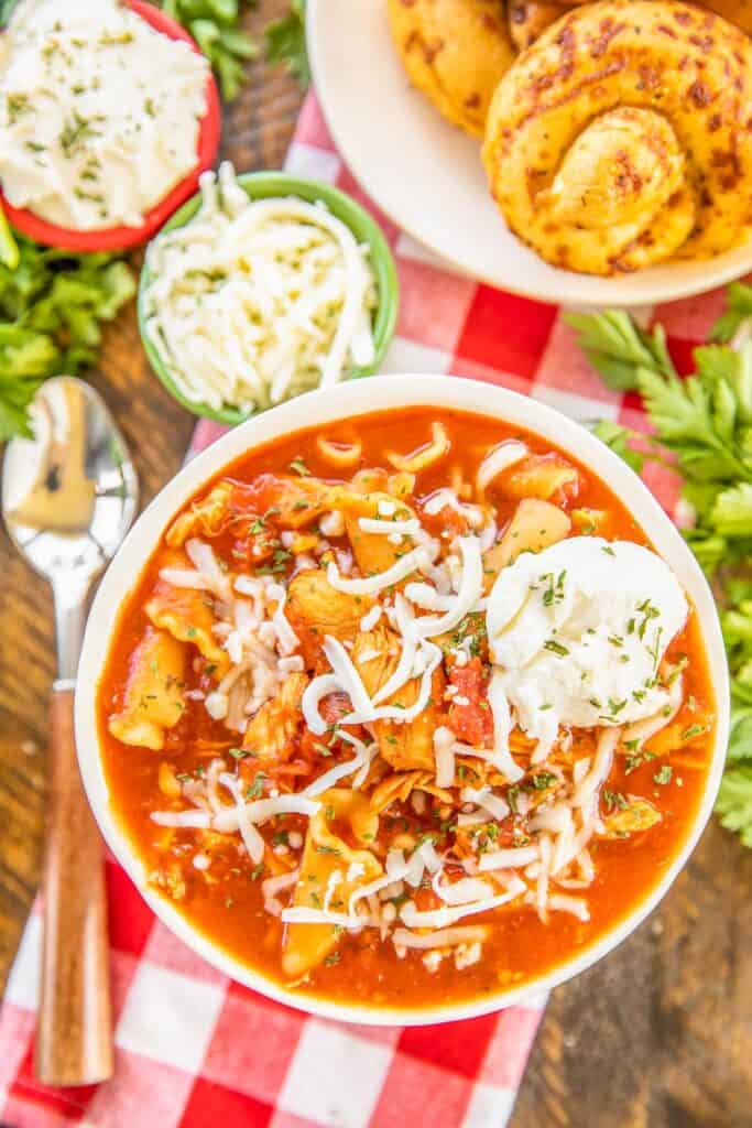 bowl of tomato, chicken and pasta soup topped with cheese