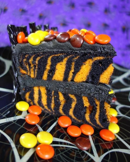 Spooktacular Halloween Cake - orange and black zebra cake surrounded with black licorice and topped with Reeses pieces. Use cake mix for a quick and festive Halloween treat!