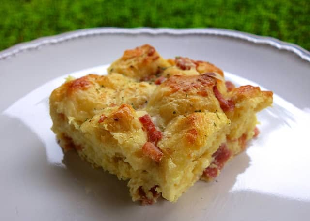 Ham and Cheese Biscuit Bake - refrigerated biscuits tossed with ham, swiss cheese, honey mustard, eggs, heavy cream and parmesan cheese. Delicious breakfast casserole! Only takes a minute to put together and is ready to eat in under 30 minutes!