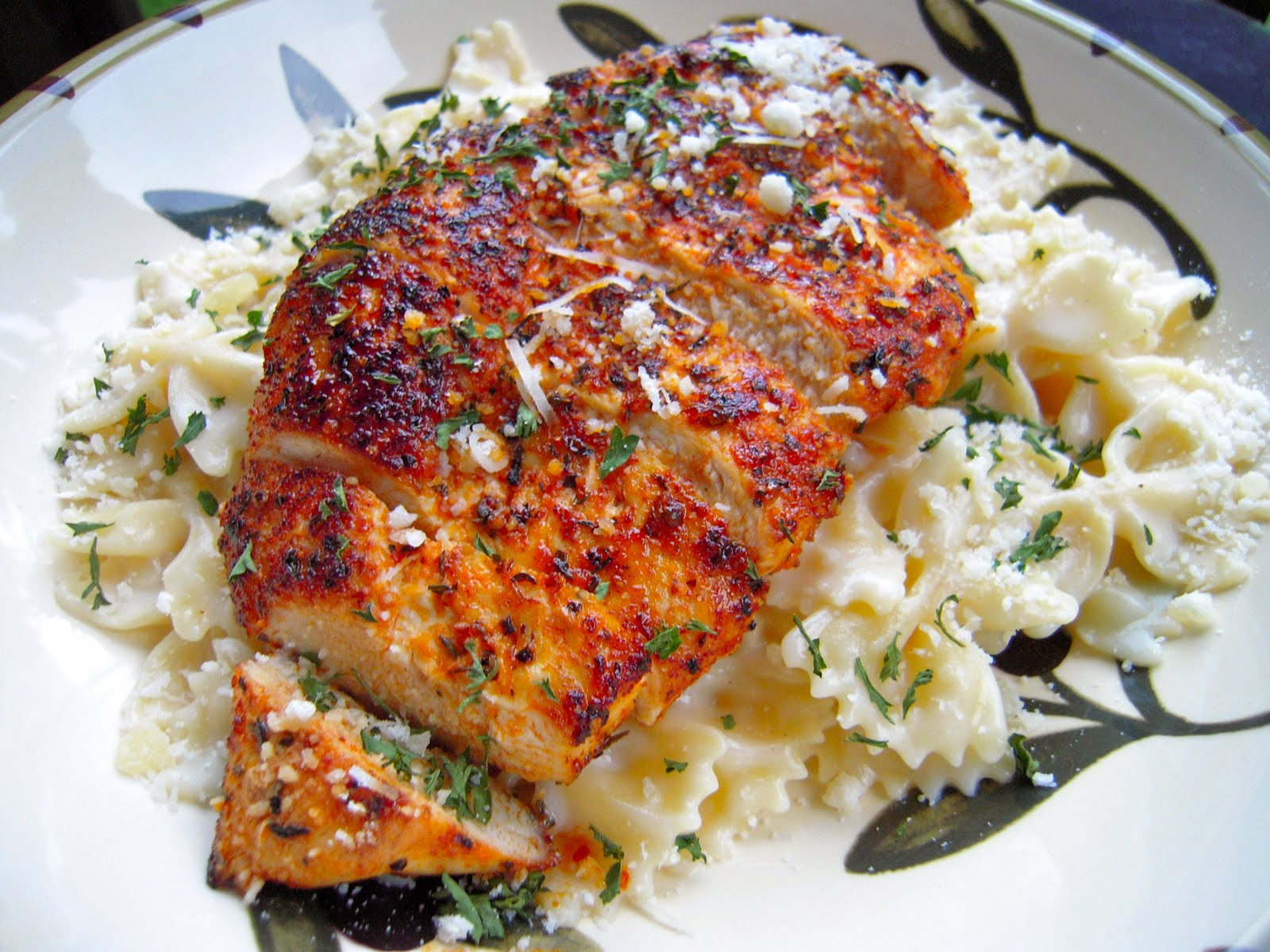 Blackened Chicken with Roasted Garlic Alfredo - so simple and SO delicious!! Chicken rubbed with cajun seasoning and pan seared. Serve over bowtie pasta tossed in roasted garlic and alfredo sauce. Better than any restaurant! Ready in under 20 minutes!!