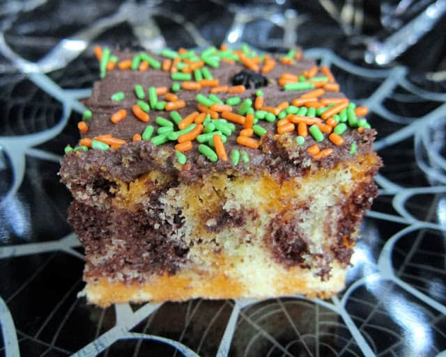 Halloween Poke Cake - perfect for all your Halloween parties!!! Chocolate marble cake, orange jello, butter, powdered sugar, coco powder, heavy cream, vanilla and halloween sprinkles. Make a day in advance and refrigerate until ready to serve. #halloween #dessert #pokecake