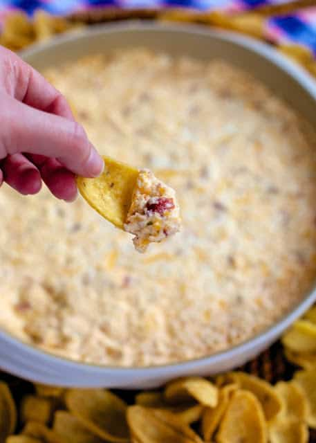 Warm Crack Dip - The ORIGINAL recipe!! Sou cream dip loaded with cheddar, bacon and ranch dip - this stuff is SO addicting! This is always the first thing to go at a party! I could make a meal out of it! Serve with Fritos and tortilla chips! Can make ahead and refrigerate before baking.