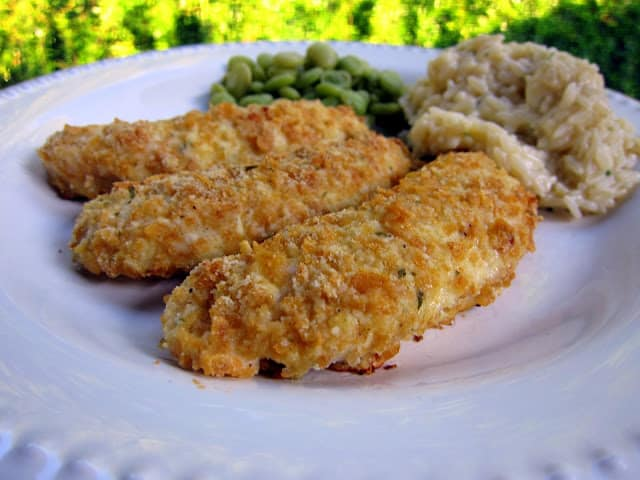 Cornflake Chicken Fingers - chicken tenders coated in crushed cornflakes, parmesan cheese and Ranch dressing mix - SO easy and SOOO good! Kids gobble these up! Ready in 15 minutes!! You can make these ahead of time and freeze them for a quick meal later.