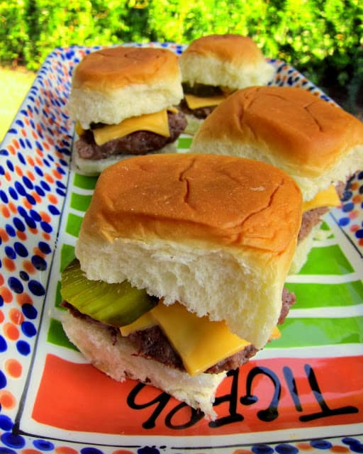 Sliders - seasoned hamburger meat baked in a 9x13-inch pan and cut into squares for sliders. SO easy! Top with your favorite hamburger toppings. Great for parties!