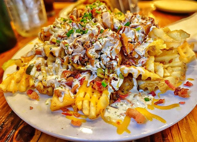 Treylor Park Grande Nachos at Treylor Park in Savannah GA- waffle fries topped with cheddar, bacon, fried chicken, pickles, chive ranch and balsamic.
