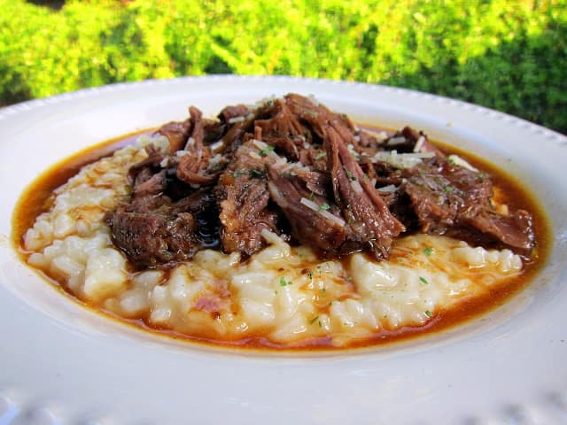 Italian Pot Roast over Parmesan Risotto - THE BEST pot roast! Pot Roast slow cooked all day in tomato juice, italian seasoning and au jus mix. Serve over a quick homemade parmesan risotto. I literally licked my plate!