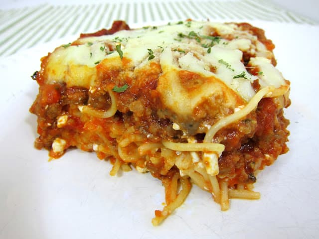 Delicious Baked Spaghetti Casserole - spaghetti, egg, parmesan, cottage cheese, sausage/hamburger, crushed tomatoes, tomato paste, spices and mozzarella - SOOO good! Baked pasta topped with a quick homemade sauce. Makes a great freezer meal!