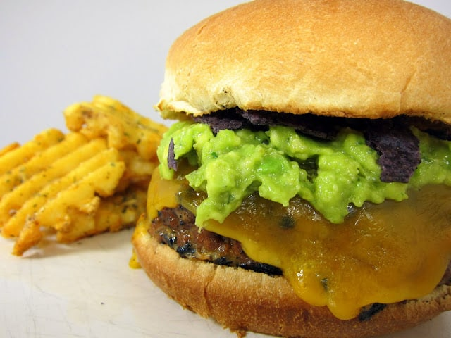 Taco Burger Recipe - hamburgers seasoned with taco seasoning and salsa - grilled and topped with cheese, guacamole and tortilla chips - SO YUM! Tacos and Burgers all in one - what's not to love?!?!