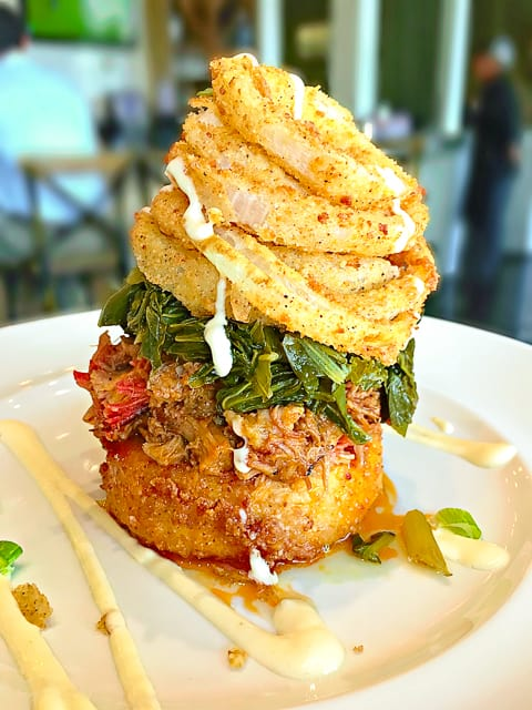 This Pulled Pork Stack from The Front Porch at Ross Bridge in Birmingham, AL is ridiculous. Fried Smoked Gouda Grit Cake topped with Pulled Pork, Turnip Greens, Onion Rings and White BBQ Sauce. WOW!