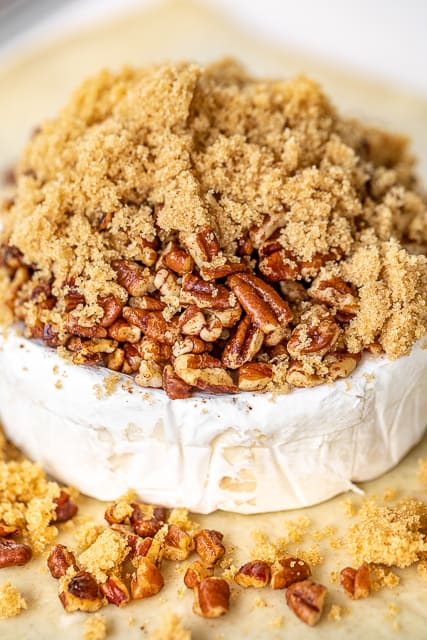brie cheese topped with brown sugar and pecans