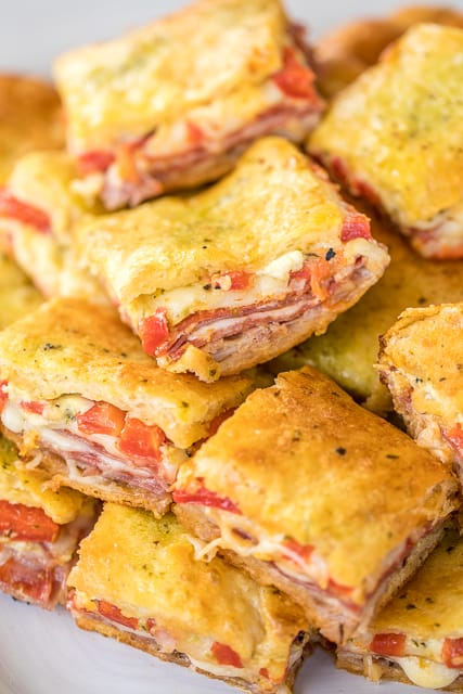Antipasto Squares recipe - SO GOOD!! Crescent rolls stuffed with ham, salami, pepperoni, provolone, swiss, and roasted red peppers. then topped with a parmesan cheese, egg and pesto mixture and baked. These things are ridiculously good!!! There are never any leftovers when I take these to party! #appetizer #partyfood #crescentrolls