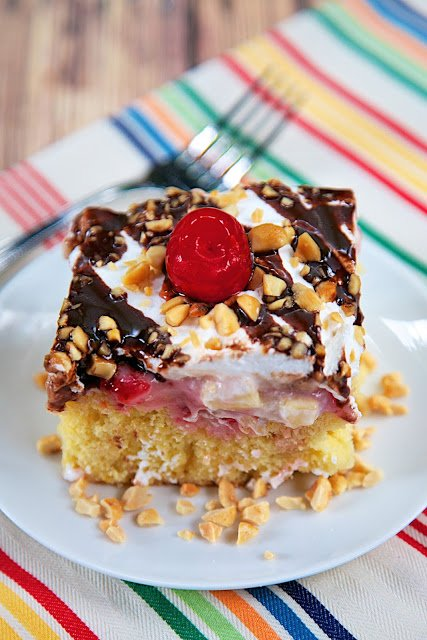 Banana Split Poke Cake Recipe - all the flavors of a banana split in cake form! Yellow cake with pineapple. strawberry ice cream topping, bananas, Cool Whip, chocolate syrup, peanuts and cherries. Can be made several days in advance. Great for a potluck!