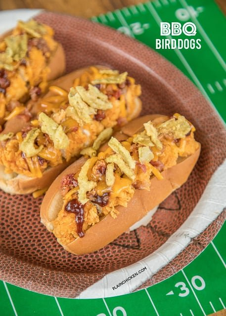 BBQ Bird Dogs - chicken fingers, bacon, cheese, BBQ sauce and fried jalapeños - perfect tailgating food! Easy to assemble in the parking lot! We also love to eat these for a quick lunch or dinner. #chicken #tailgatingrecipe #easychickenrecipe #chickenrecipe #chickenfingers #bbq