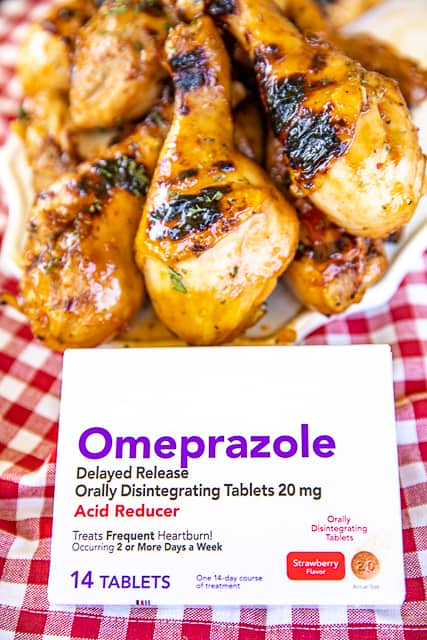 box of omeprazole with chicken drumsticks in background