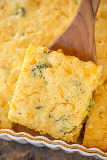 taking a piece of cornbread out of the baking dish