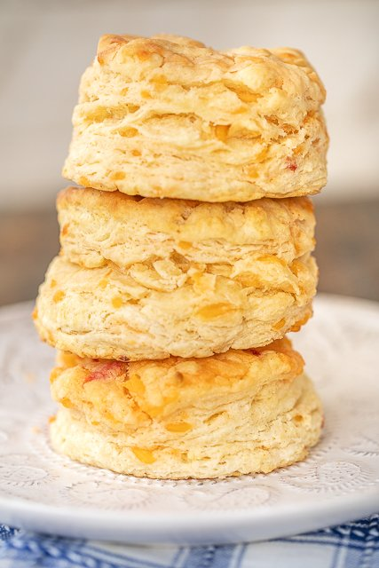three freshly baked biscuits stacked on a plate