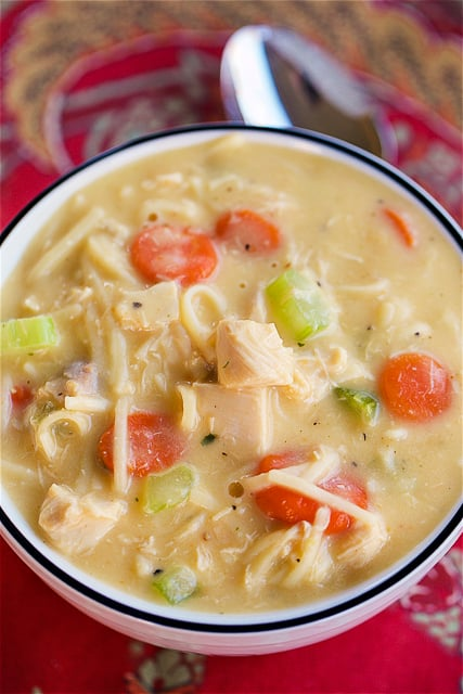 Cheesy Chicken Noodle Soup - ready in under 30 minutes! Just dump everything in the pot and let it simmer. SO easy! We LOVE this soup!!! Chicken, cheese soup, chicken broth, milk, celery, carrots, egg noodles and cheddar cheese. We make this at least once a month.