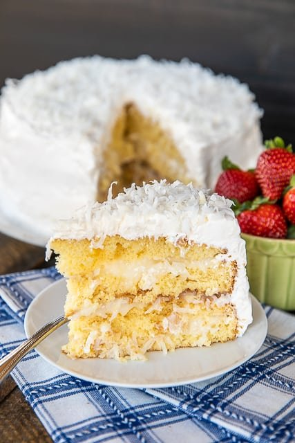 Coconut Cake - the sour cream cool whip frosting makes this cake! It is AMAZING!!! So easy to make and everyone loves it! This is my go-to cake for holidays and parties. Everyone always asks for the recipe! Only 5 ingredients -Cake mix, sour cream, cool whip, coconut and sugar. The frosting has to sit overnight in the refrigerator, so plan ahead to make this easy Coconut Cake! #cake #coconutcake #dessert #recipe