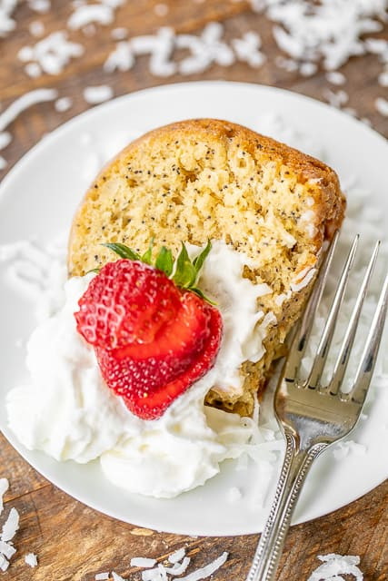 slice of poppy seed cake on a plate with strawberries