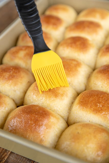 brushing homemade rolls with butter