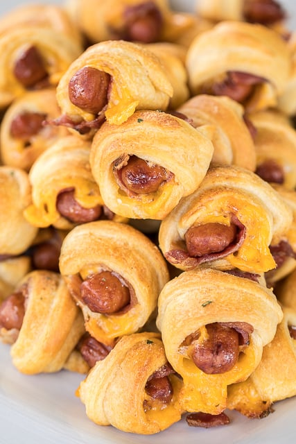 Crack Pigs in a Blanket - pigs in a blanket loaded with cheddar, bacon and ranch - OH MY GOODNESS!!! Only 5 ingredients and ready in about 15 minutes. Great for parties! These things FLY off the plate!!! I almost always double the recipe! #superbowl #tailgating #pigsinablanket