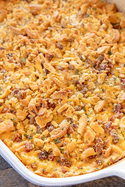 Creamy Crack Potatoes - creamy potatoes loaded with cheddar, bacon and ranch! SO good! Frozen shredded hash browns, cheddar, bacon, ranch dressing mix, sour cream, cream of chicken soup, heavy cream, butter and ritz crackers. A cross between scalloped potatoes and a regular potato casserole. I could make a meal out of these potatoes!!! Can make ahead and freeze for later. Great for a crowd. #potatocasserole #sidedish #freezermeal #bacon
