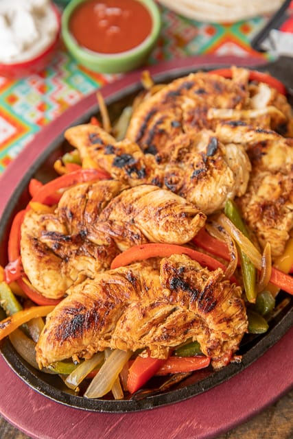 Easy Chicken Fajitas - SO much better than the Mexican restaurant and only 5 ingredients! We make these every week - great meal prep recipe! Chicken, Italian dressing, diced tomatoes and green chiles, taco seasoning and lime. Let the chicken marinate overnight and quickly cook in the skillet. Add onions and peppers for an authentic Mexican restaurant taste. SO easy and SO good! #mexican #chicken #chickenfajitas #mealprep