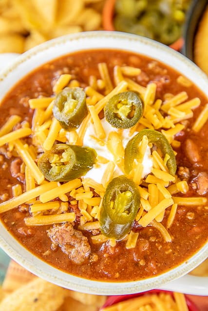 a bowl of chili topped with sour cream, cheese, and jalapenos