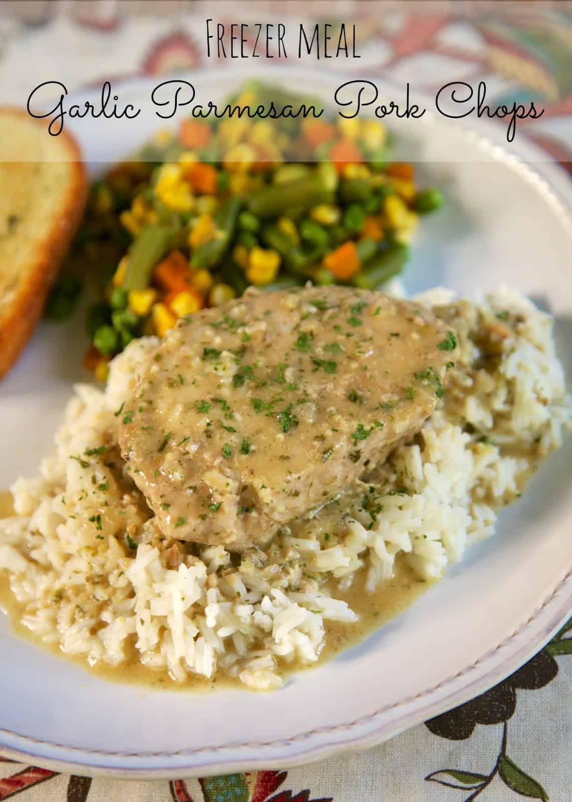 {Freezer Meal} Garlic Parmesan Pork Chops - SO delicious!!! Pork chops slow cooked in garlic seasoning, onion flakes, cream of chicken soup and apple juice. Seriously the most delicious pork chops we've ever eaten!! Can cook frozen in the slow cooker. #porkchops #slowcooker #freezermeal