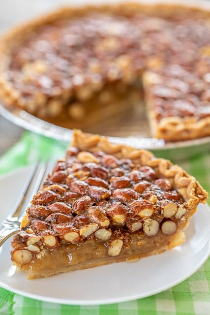 Georgia Peanut Pie - very similar to a pecan pie but with raw peanuts! SO good! This pie is SO easy to make - just whisk together eggs, vanilla, sugar and corn syrup. Stir in the raw peanuts and pour into a frozen deep dish pie crust. Top baked pie with some vanilla ice cream or fresh whipped cream. Can make in advance and store in an air-tight container. #pie #peanut #pecanpie #dessert #peanutpie