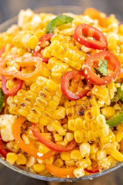 Grilled Corn Salad - simple and delicious side dish! Grilled corn, sweet peppers, jalapeños, feta cheese tossed in honey, lime, olive oil, garlic, and  cumin. Great with all your grilled dishes! Will keep in the refrigerator for several days. I made this for a cookout and it was gone in a flash!! YUM! #grilling #vegetable #sidedish #corn