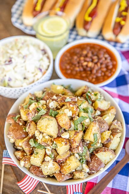 grilled potato salad, hot dogs, baked beans on a table