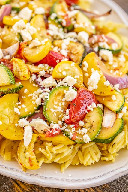 Grilled Vegetable Orzo Salad - so much amazing flavor! A great side dish or meatless main dish. Orzo, chicken broth, rosemary, olive oil, red onion, squash, zucchini, roma tomatoes, tossed in cider vinegar, olive oil, parsley, thyme, rosemary, salt and feta. Comes together in under 30 minutes. Can mix up the vegetables to your favorites. Good eaten warm or cold. YUM! #grilling #vegetables #grill #sidedish #meatlessmaindish