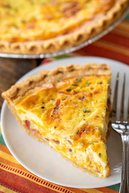 Honey Ham and Cheese Quiche - can be made ahead of time and refrigerated and even frozen for later. Great for breakfast, lunch or dinner! Ham, cheese, eggs, honey mustard, sour cream, heavy cream and pepper. Great way to use up leftover holiday ham. This never lasts long in our house!