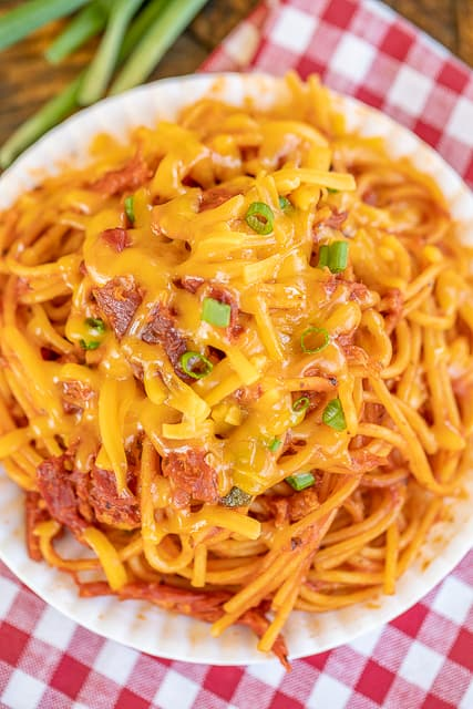 bbq spaghetti topped with cheese and onions on a plate