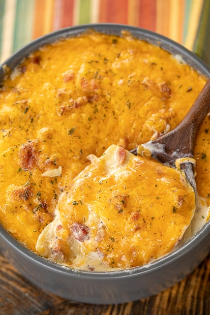 Instant Pot Scalloped Crack Potatoes - potatoes loaded with cheddar, bacon and ranch. So simple and they taste amazing! Everyone LOVES these cheesy potatoes. Thinly sliced potatoes, heavy cream, milk, ranch seasoning, cheddar cheese and bacon. Great with chicken, pork, steak and burgers! SO good! #instantpot #potatoes #bacon