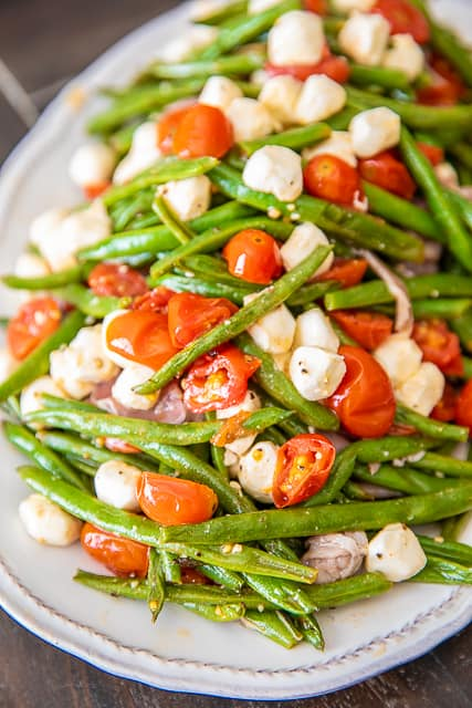 Italian Green Bean Salad - quick and delicious side dish! Green beans, tomatoes, garlic, olive oil, prosciutto, and mozzarella tossed in lemon juice and olive oil. Can serve hot or cold. Great for potlucks and cookouts. Can make in advance and refrigerate until ready to serve. Everyone always asks for the recipe! YUM! #salad #greenbeans #vegetable